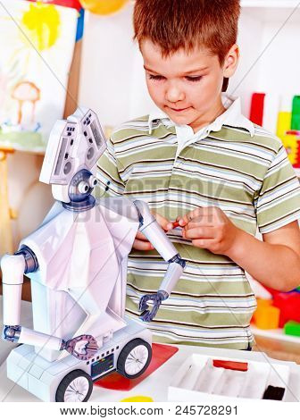 Child build robot toy. Kid engaged in robotics in programming classes. Boy is programming own tech smart toys with artificial intelligence at school.