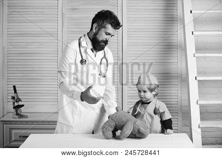 Vet And Little Assistant Make An Injection To Teddy Bear Man With Beard And Boy Hold Syringe On Wood
