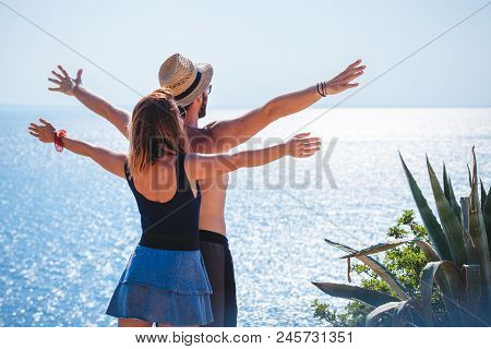 Young Couple Enjoying The View By The Sea