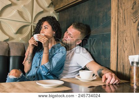 Happy Young Couple Is Drinking Coffee And Smiling While Sitting At The Cafe. I Love You. Romantic Be
