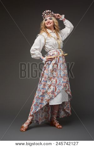 Goddes of ethnofuturism. Beautiful blonde woman in white folklore costume poster