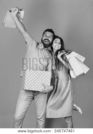 Couple In Love Holds Shopping Bags On Yellow Background. Man With Beard Holds Red Polka Dotted Box.