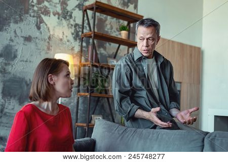 Piece Of Advice. Caring Concerned Man Coming To His Experienced Wife For Piece Of Advice While Sitti