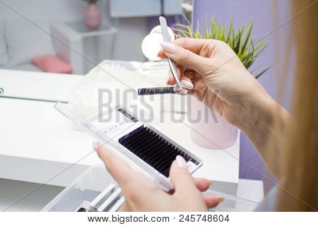 Beauty And Fashion Concept - Eyelash Extension Procedure. Woman Hands Closeup With Tool For Eyelash