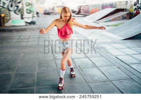 Well-built And Slim Girl Is Posing On Camera. She Is Looking Down To Her Knees And Rollerblading. Sh