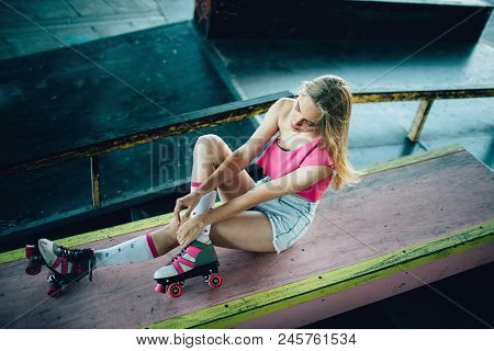 Well-built And Slim Girl Is Posing. She Is Sitting And Holding Her Hands On Right Leg. Girl Is Looki