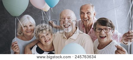 A Group Of Happy, Senior Friends Holding Colorful Balloons While Posing At A Party And Celebrating B