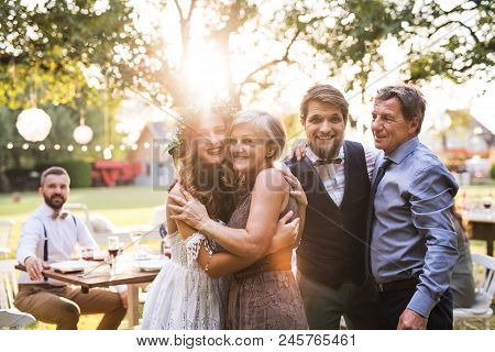 Wedding Reception Outside In The Backyard. Family Celebration. Bride, Groom With Parents Posing For