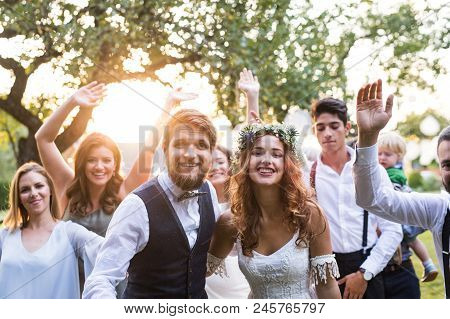 Wedding Reception Outside In The Backyard. Family Celebration. Bride, Groom And Their Guests Posing