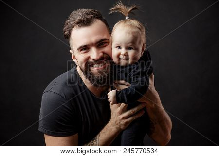 Handsome Athletic Man With Adorable Funny Infant Baby Looking At Camera On Black Background. Parenth