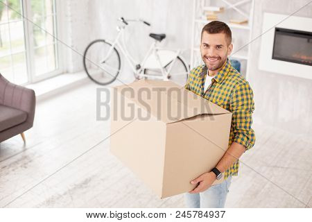 My Own Home. Jovial Confident Man Holding Box And Smiling To Camera