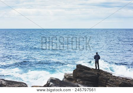 Young Man Holds A Fishing Rod And Catches Fish In The Nature On A Sea Background, Hipster Fisherman