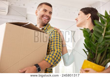 Cosy Home. Low Angle Of Positive Vigorous Couple Carrying Belongings And Laughing