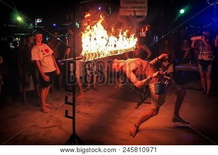 Phi Phi Island, Thailand, November 13, 2017: A Merry Youth People Limbos Under A Bar Of Fire. Crowd