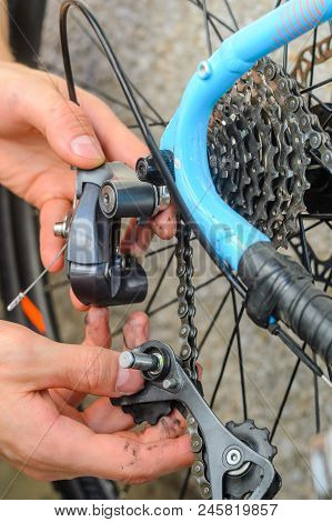 Broken Bicycle Rear Derailleur. Hands Hold The Parts Of The Rear Derailleur, Which Fell Apart In Hal