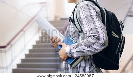 Student With Backpack And Books On The Background Of The Ladder At The Institute.