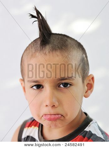 Cute little boy with funny hair and cheerful grimace
