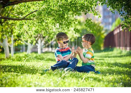 Happy Summer Holidays. Two Happy Children On A Green Lawn At A Summer Park.