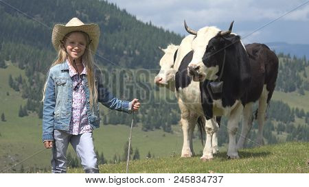 Portrait Of Smiling Farmer Child Pasturing Cows, Cowherd Girl With Cattle, Kid Playing Outdoor In Na