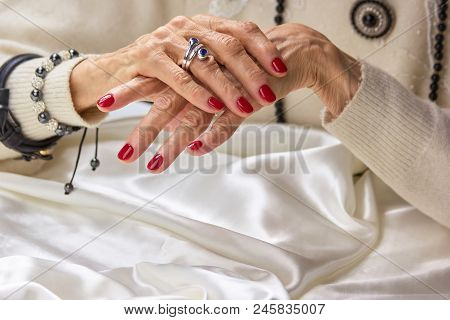 Red Manicure On Old Womans Hands. Senior Woman Hands With Red Nails And Luxury Jewelry. Aged Beautif