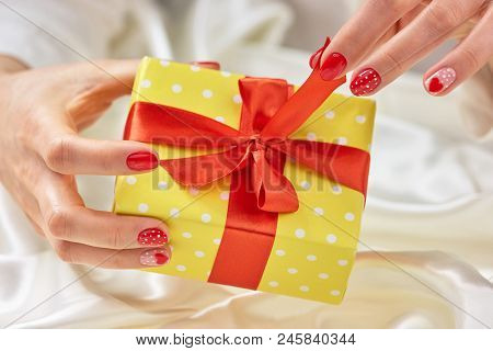 Female Hands Unpacking Gift Box. Young Woman Manicured Hands Opening Yellow Gift Box. Birthday Prese