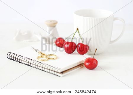 Feminine Still Life Composition. Porcelain Cup Of Coffee, Sweet Red Cherry Fruit, Blank Notebook, Go