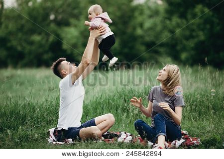 Happy Family Playing Together, Parents With Their Little Child Relaxing In Nature. Father Raising Ba