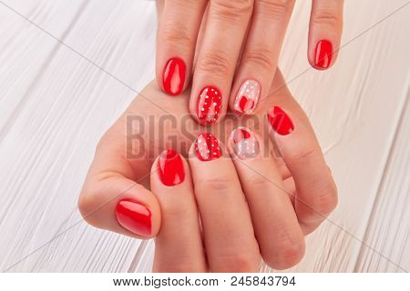 Female Hands With Beautiful Designed Manicure. Young Woman Gentle Manicured Hands With Red Hearts An