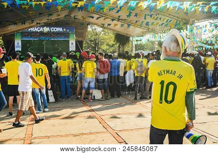Old Man Wearing Green And Yellow Watching A Match Of The World Cup