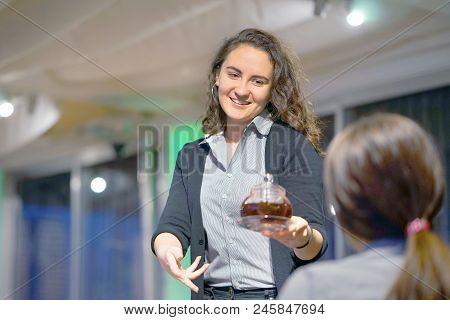 The Waitress Is Carrying Tea. Hospitable Girl Waitress Is Carrying Tea And Tea Glass Teapot To The C
