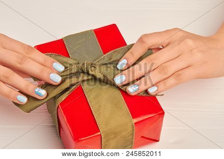 Red Gift With Green Ribbon. Female Hands With Beautiful Winter Manicure Unpacking Box With Gift. Hol