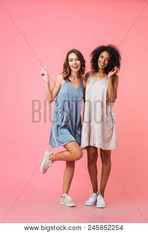 Full length portrait of two pretty smiling girls in dresses standing together isolated over pink background