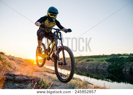 Professional Cyclist Riding the Downhill Mountain Bike on the Summer Rocky Trail at Sunset. Extreme Sport and Enduro Cycling Concept.