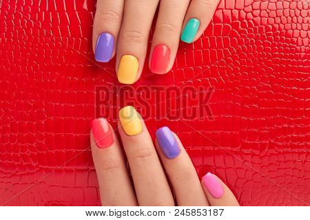 Multicolored Manicure And Red Lacquered Background. Female Fingers With Colorful Summer Nail Polish