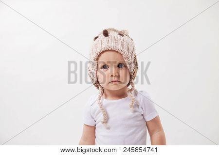 Portrait Of A Beautiful Baby Girl In A Huge Knitted Hat. Isolated On White Background.