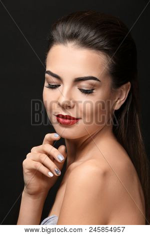 Young woman with beautiful eyebrows on black background