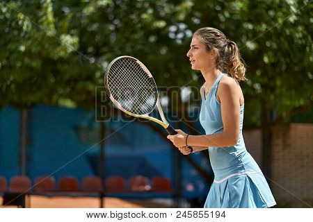 Sportive Girl Plays Tennis On The Court Outdoors. She Stands With A Racket In The Hands. Woman Wears