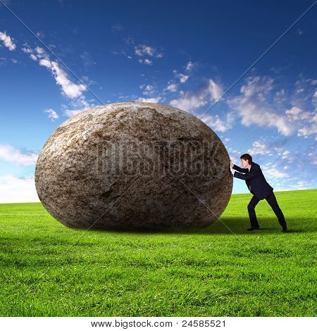 Image of businessman rolling a giant stone
