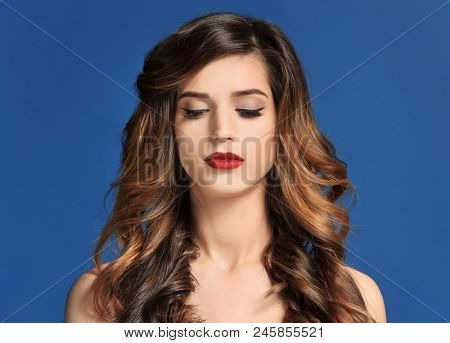 Attractive young woman with elegant makeup and long eyelashes on color background. Eyelash extensions