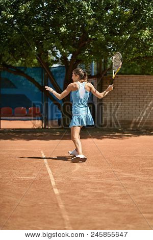 Cute Girl Plays Tennis On The Court Outdoors. She Prepares To Beat Off A Ball. Woman Wears A Light B