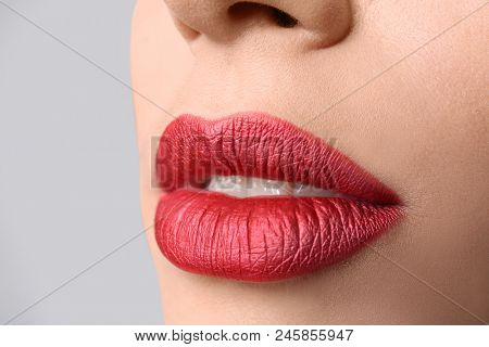 Young woman with bright lip makeup on grey background, closeup