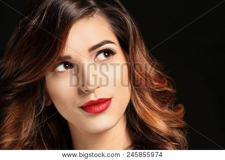 Attractive young woman with elegant makeup and long eyelashes on black background. Eyelash extensions