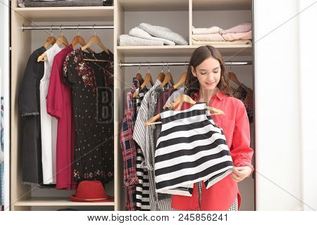 Teenage girl trying on blouse near wardrobe at home