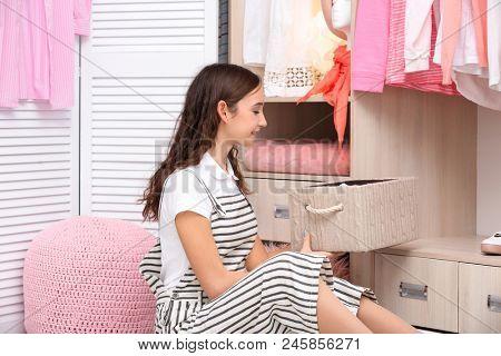 Teenage girl choosing clothes near wardrobe at home