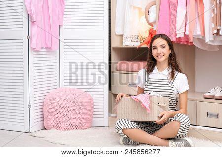 Teenage girl sitting on floor near wardrobe at home