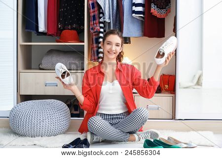 Beautiful girl choosing shoes near wardrobe at home
