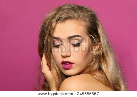 Young woman with beautiful eyebrows on color background