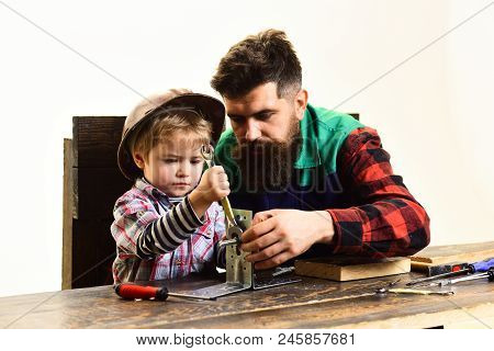 Repair, assistance, fatherhood concept - son&father repairing together. Boy connects metal plates parts with bolt. Children's creativity&engineering education - boy in workshop connects steel plates. poster