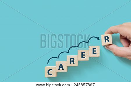 Hand Putting Wooden Cube Block On Blue Background With Word Career And Copy Space For Your Text. Bus