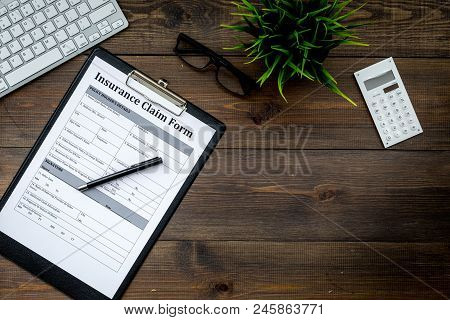 Insurance Event Concept. Insurance Claim Form On Dark Wooden Office Desk Top View.